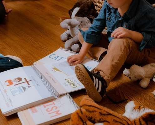 boy on floor with catechism book and stuffed animals