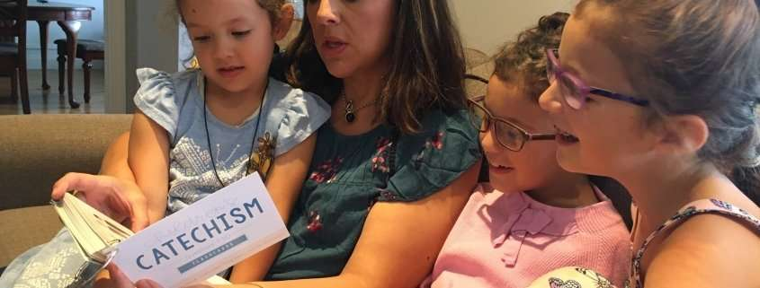 mom teaching children the catechism at home