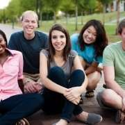group of smiling young adults sitting on the ground