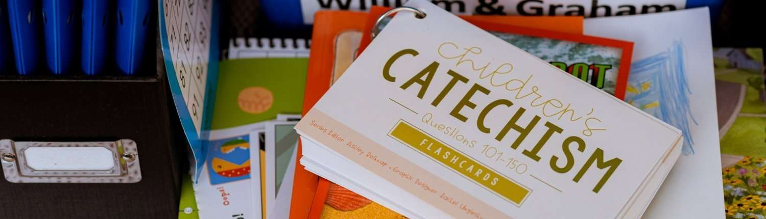 catechism flashcards questions 101-150 on stack of children's books