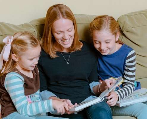 mom and two daughters learning from catechism flashcards
