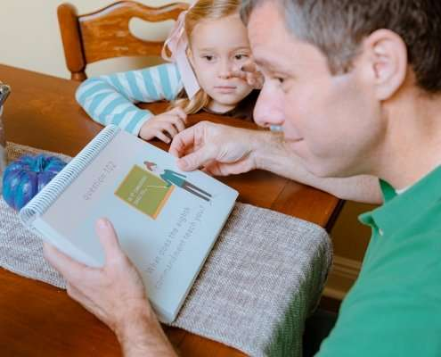 dad reviewing question 102 of the catechism book with his daughters