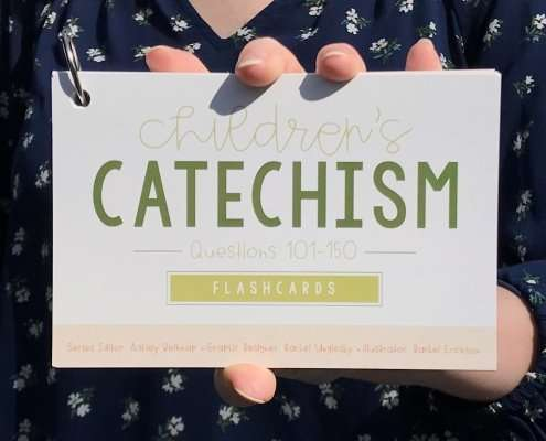 girl holding catechism flashcard Questions 101-150 set in front of her
