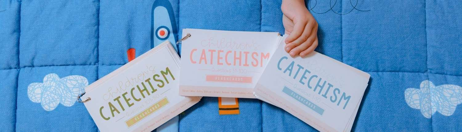all three catechism flashcard sets laying on a bed with child's hand holding one set