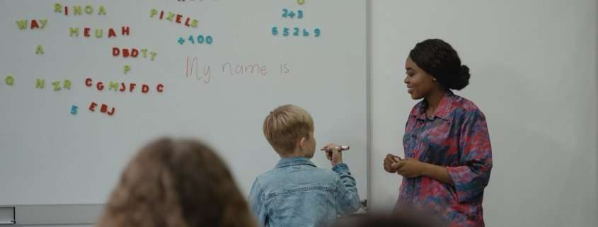 teacher and student standing in front of a whiteboard